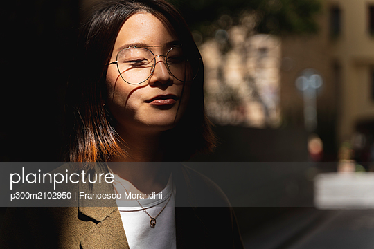 Portrait of young woman with closed eyes wearing glasses in sunlight - p300m2102950 by Francesco Morandini