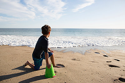 Boy looking at sea while sitting with bucket on beach during sunny day - p1166m1182983 by Cavan Images