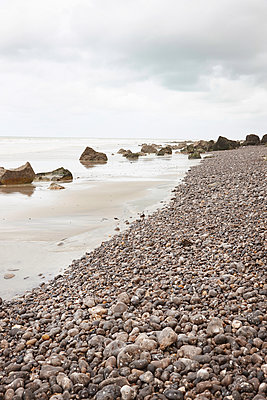 Strand mit Kieselsteinen und Felsbrocken im Wasser - p1198m1132134 von Guenther Schwering