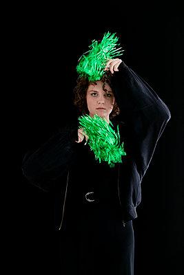 Junge Frau mit grünen Cheerleaderpompons - p1212m1120241 von harry + lidy