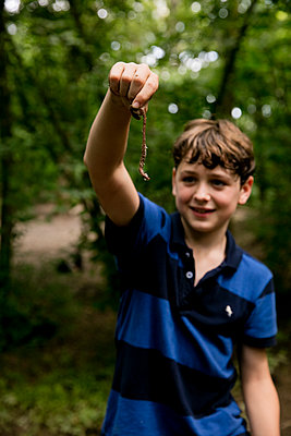 Boy in forest showing earthworm - p1212m1152941 by harry + lidy