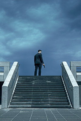 Man in Suit with Gun at Top of Stairs  - p1248m2134698 by miguel sobreira