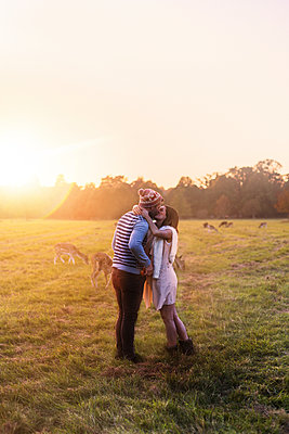 Couple kissing with deers on a meadow at sunset - p300m1101172f by Boy photography