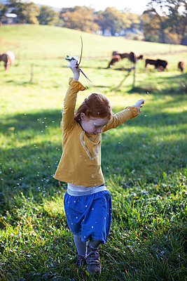 Redheaded girl dancing in field with blowball - p300m2103388 von Anette Christina Götz