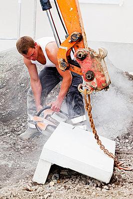 Men working with corner stones during house building - p300m798133f by Dieter Heinemann