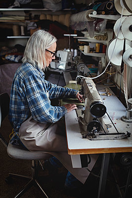 Senior owner using sewing machine at workshop - p426m1543006 by Maskot