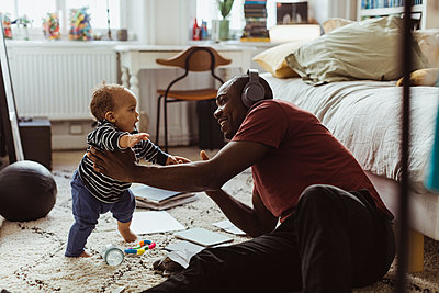 Father holding male toddler while sitting in bedroom at home - p426m2279800 by Maskot