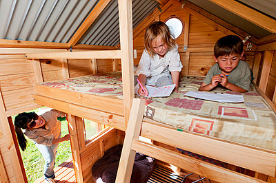Mother looking in on children in playhouse - p924m664824f by Flashgun