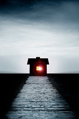 Old house with light in window and wooden pier - p975m2278177 by Hayden Verry