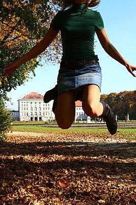 Huepfende Frau im Mini Rock in einem Park - p9791463 von Einecke