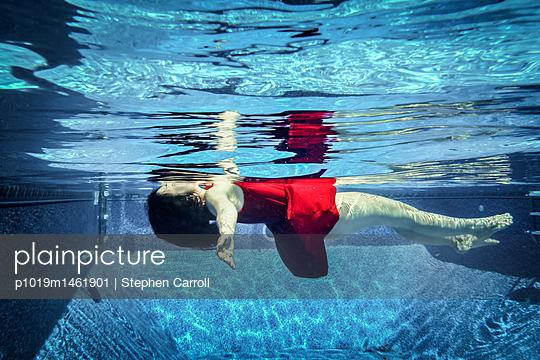 Woman in red dress floating underwater - p1019m1461901 by Stephen Carroll