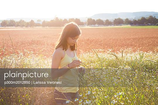 Young girl standing on meadow at summer evening - p300m2012850 von Larissa Veronesi