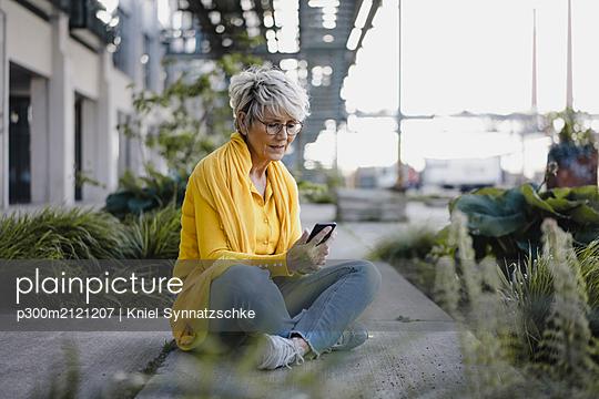 Mature woman using smartphone outdoors - p300m2121207 by Kniel Synnatzschke