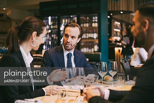 Confident businessman talking to businesswoman in restaurant - p426m2212097 by Maskot