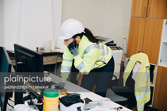 Female engineer wearing hardhat talking on smart phone while leaning on desk in office - p426m2295979 by Maskot