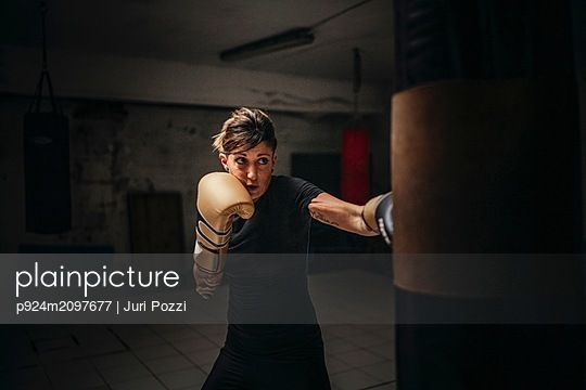 Boxer training with sandbag in gym - p924m2097677 by Juri Pozzi