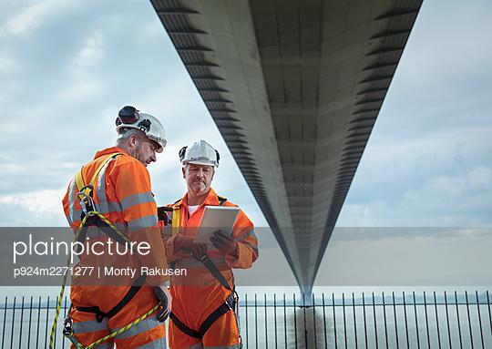 UK, East Yorkshire, Two engineers looking at tablet under bridge - p924m2271277 by Monty Rakusen