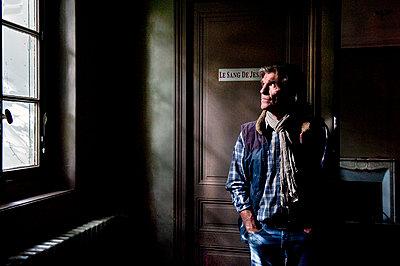 Man looking through the window - p1307m1225125 by Agnès Deschamps