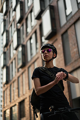 Woman cyclist looks at side on background of brick building in summer - p1630m2196894 by Sergey Mironov
