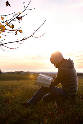 Germany, woman reading a book on an autumnal meadow at sunrise - p300m1115166f by Miriam Dörr