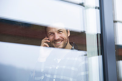 Smiling construction worker talking over smart phone seen through window at construction site - p300m2214116 by MiJo