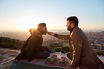 Man feeding croissant to boyfriend while sitting on observation point against city, Bunkers del Carmel, Barcelona, Spain - p300m2257335 by Veam