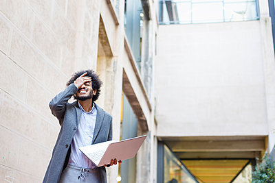 Disappointed male entrepreneur holding laptop while standing in front of building - p300m2277096 by Ignacio Ferrándiz Roig