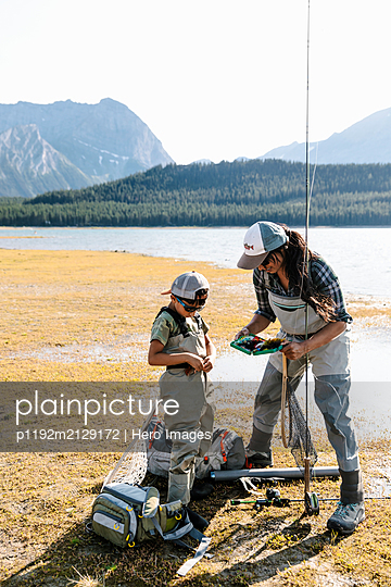 Mother and son fishing at sunny lakeside - p1192m2129172 by Hero Images