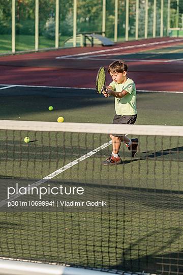 Boy playing tennis on field