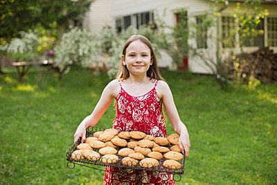 Baking homemade cookies. A young girl holding a tray of fresh baked cookies.  - p1100m875935f by Bill Miles