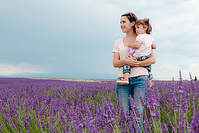 Happy mother and daughter walking among lavender fields in the summer - p1166m2136641 by Cavan Images