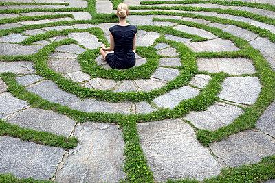 Italy, Alto Adige, Lana, woman sitting in natural open air maze meditating - p300m2083946 von Petra Stockhausen