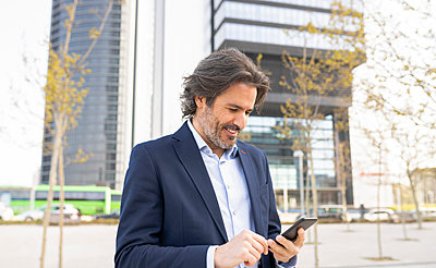 Smiling businessman using smart phone in city - p300m2282133 by Jose Carlos Ichiro