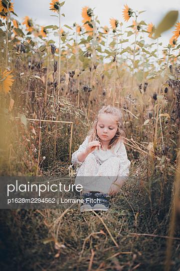 Kleines Mädchen im Sonnenblumenfeld - p1628m2294562 von Lorraine Fitch