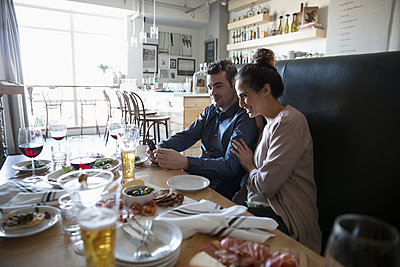 Young couple with smart phone at bar table - p1192m1567187 by Hero Images
