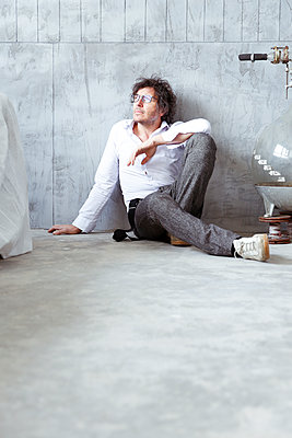 Architect sitting on the floor at construction site - p300m1416751 by realitybites