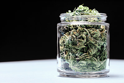 Marijuana leaves in glass jar on table against black background - p301m1579825 by Norman Posselt