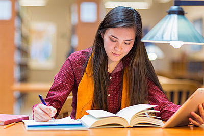 Mixed race student studying in library - p555m1413748 by Marc Romanelli