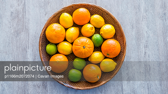Above view of fruit basket on a table with mandarins and a melon - p1166m2072074 by Cavan Images