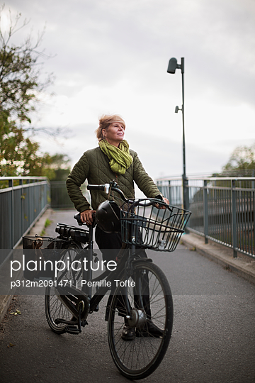 Young woman with bicycle - p312m2091471 by Pernille Tofte
