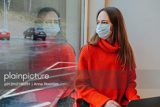 Woman wearing protective mask looking through window - p312m2190291 by Anna Roström
