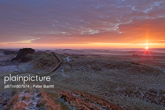 Sunrise and Hadrian's Wall National Trail in winter, looking to Housesteads Fort, Hadrian's Wall, UNESCO World Heritage Site, Northumberland, England, United Kingdom, Europe - p871m807574 by Peter Barritt