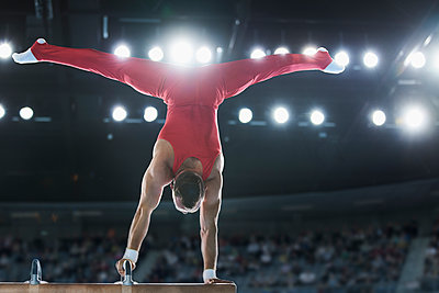 Male gymnast performing upside-down handstand on pommel horse - p1023m1217736 by Chris Ryan