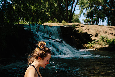Close up of teen girl walking standing near a small waterfall - p1166m2233030 by Cavan Images