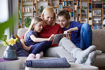 Mother and her daughters sitting on couch, having fun  using digital laptop - p300m2004622 von Rainer Berg