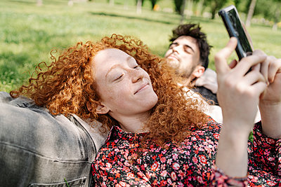 Smiling woman using smart phone while lying on boyfriend in park - p300m2287586 by COROIMAGE