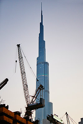 Building cranes with skyscraper on background - p312m1024742f by Magnus Ragnvid