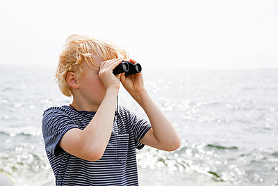 Sweden, Stockholm Archipelago, Sodermanland, Orno, Boy (8-9) looking through binoculars - p352m1349492 by Jenny Lagerqvist