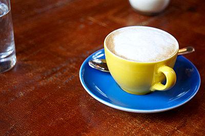 Caffé latte on wooden table - p4902312 by Andrea Altemüller