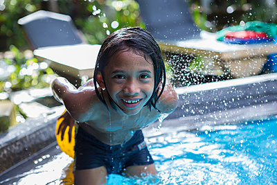 Balinese boy playing in swimming pool - p555m1419390 by Marc Romanelli